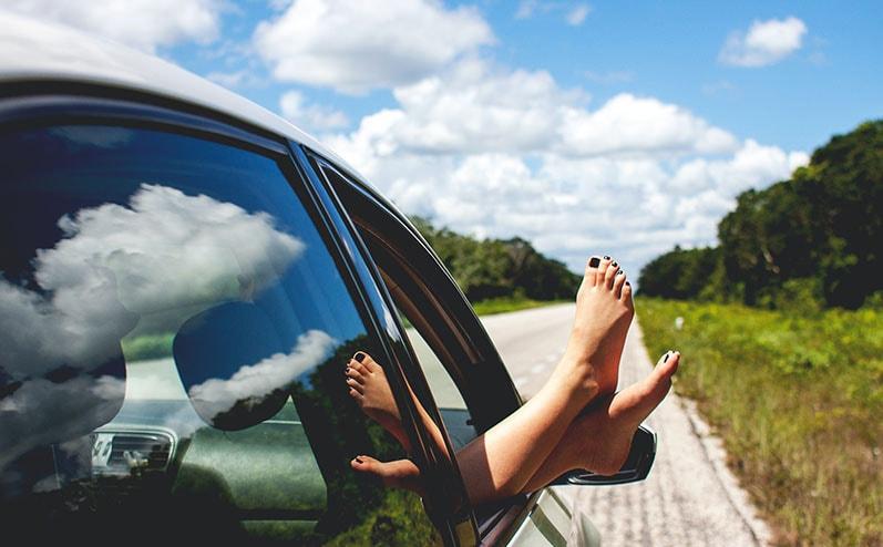 kājas pa auto logu